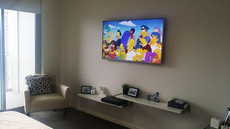 TV installation design ideas with floating shelves mounted below.